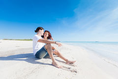 Young Couple Sitting in a Caribbean Beach Stock Image