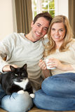 Young couple sitting with cat on sofa Stock Photo