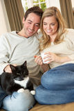 Young couple sitting with cat on sofa Stock Photos