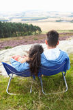 Young Couple Sitting In Chairs On Camping Trip Stock Image