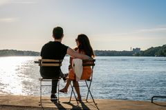 A young couple sitting on chairs at a quay by the water looking at the sunset. stock photo