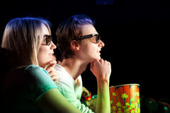Young couple sitting at the cinema, watching a film Royalty Free Stock Photos