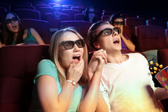 Young couple sitting at the cinema, watching a horrors film Stock Images
