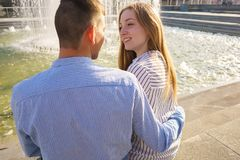 Young couple sitting close in sunlight, smiling and talking. Rel stock photo