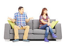 Young couple sitting on a couch during an argument Royalty Free Stock Image
