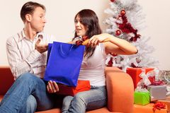 Young Couple Exchanging Christmas Gifts. A young couple is sitting on the couch and exchanging christmas gifts. she seems to be quite surprised by the rolling Stock Photography