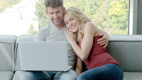 Young Couple Sitting On Couch With Laptop stock video footage