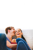Young couple sitting at couch and laughing Stock Image