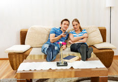 Young couple sitting on couch and watching TV Royalty Free Stock Photos