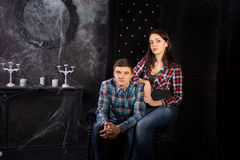 Young Couple Sitting in Creepy High Back Chair Royalty Free Stock Image