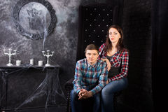 Young Couple Sitting in Creepy High Back Chair Royalty Free Stock Photography