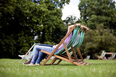A young couple sitting on deckchairs in St James Park Royalty Free Stock Photo