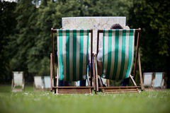A young couple sitting on deckchairs in St James Park, looking at a map Stock Image