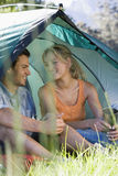 Young couple sitting in dome tent, holding camping mugs, smiling (differential focus) Royalty Free Stock Photos