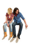 Young couple sitting on a empty banner Royalty Free Stock Photo
