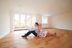 Young Couple Sitting In Empty Room Of Dream House Stock Image