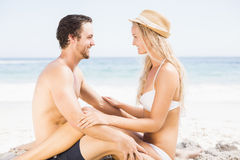 Young couple sitting face to face on the beach Royalty Free Stock Photos