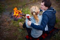 Young couple sitting by the fire and drinking tea. Royalty Free Stock Photos