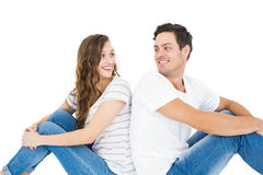 Young couple sitting on floor back to back. On white background Stock Photography