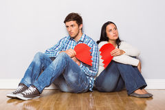Young couple sitting on floor with broken heart Royalty Free Stock Photo