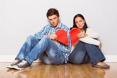 Young couple sitting on floor with broken heart Royalty Free Stock Photography