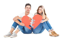 Young couple sitting on floor with broken heart Stock Photo