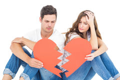 Young couple sitting on floor with broken heart Stock Images