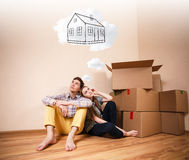 Young couple sitting on the floor and daydream. About new home Stock Photography