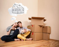 Young couple sitting on the floor and daydream. About new home Royalty Free Stock Photo