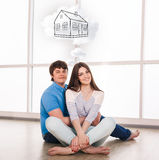Young couple sitting on the floor and daydream. About new home Royalty Free Stock Image