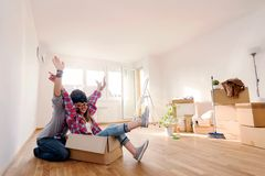 Young couple sitting on the floor of empty apartment. Move in to new home. Happy young couple sitting on the floor of empty apartment. Move in to new home Stock Photography