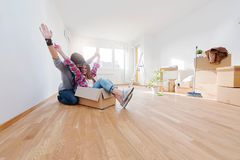 Young couple sitting on the floor of empty apartment. Move in to new home. Happy young couple sitting on the floor of empty apartment. Move in to new home Stock Photos