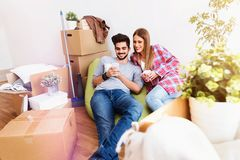 Young couple sitting on the floor of empty apartment. Move in to new home. Happy young couple sitting on the floor of empty apartment. Move in to new home Stock Photo