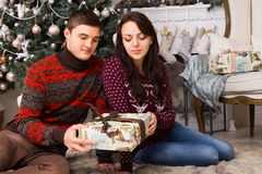 Young Couple Sitting on the Floor Holding One Gift Stock Images