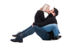 Young couple sitting on floor hugging and kissing Stock Photography