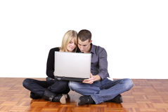 Young couple sitting in the floor with a laptop Royalty Free Stock Image