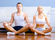 Young Couple Sitting on Floor Meditating Stock Images