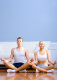 Young Couple Sitting on Floor Meditating Stock Photos