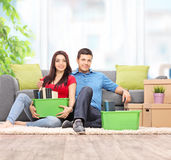 Young couple sitting on the floor with moving boxes Stock Image