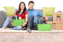 Young couple sitting on the floor with moving boxes Royalty Free Stock Image