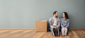 Young couple sitting on floor near box indoors. Moving into new house stock images