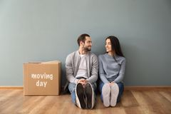 Young couple sitting on floor near box indoors. Moving into new house royalty free stock images