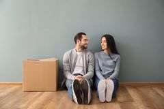 Young couple sitting on floor near box indoors. Moving into new house stock photos