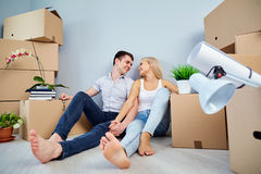 A young couple is sitting on the floor of a new apartment house. royalty free stock photos