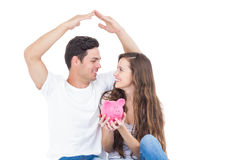 Young couple sitting on floor with piggy bank Stock Photos
