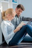 Young Couple Sitting on Floor Reading Book Royalty Free Stock Photo