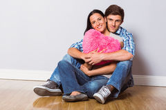 Young couple sitting on floor smiling Royalty Free Stock Images