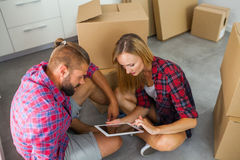 Young couple sitting on the floor with tablet pc and choosing fu Stock Photography
