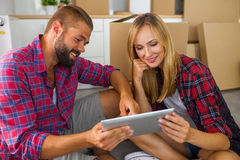 Young couple sitting on the floor with tablet pc and choosing fu Royalty Free Stock Photography