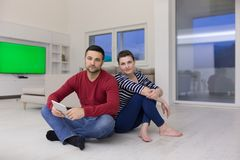 Young Couple using digital tablet on the floor Stock Images